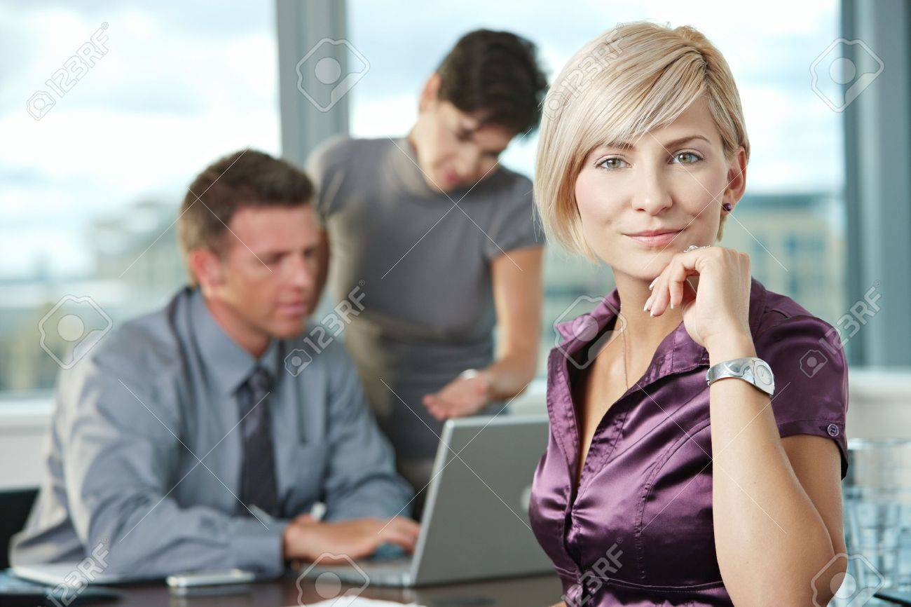 Smiling businesswoman on business meeting at office with team in background. Stock Photo - 6285873