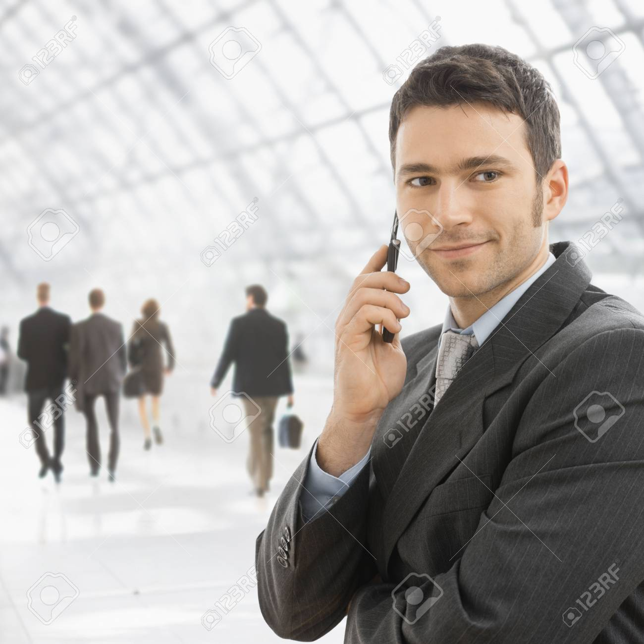 Closeup portrait of happy businessman talking on mobile in front of office building windows. Stock Photo - 6286136
