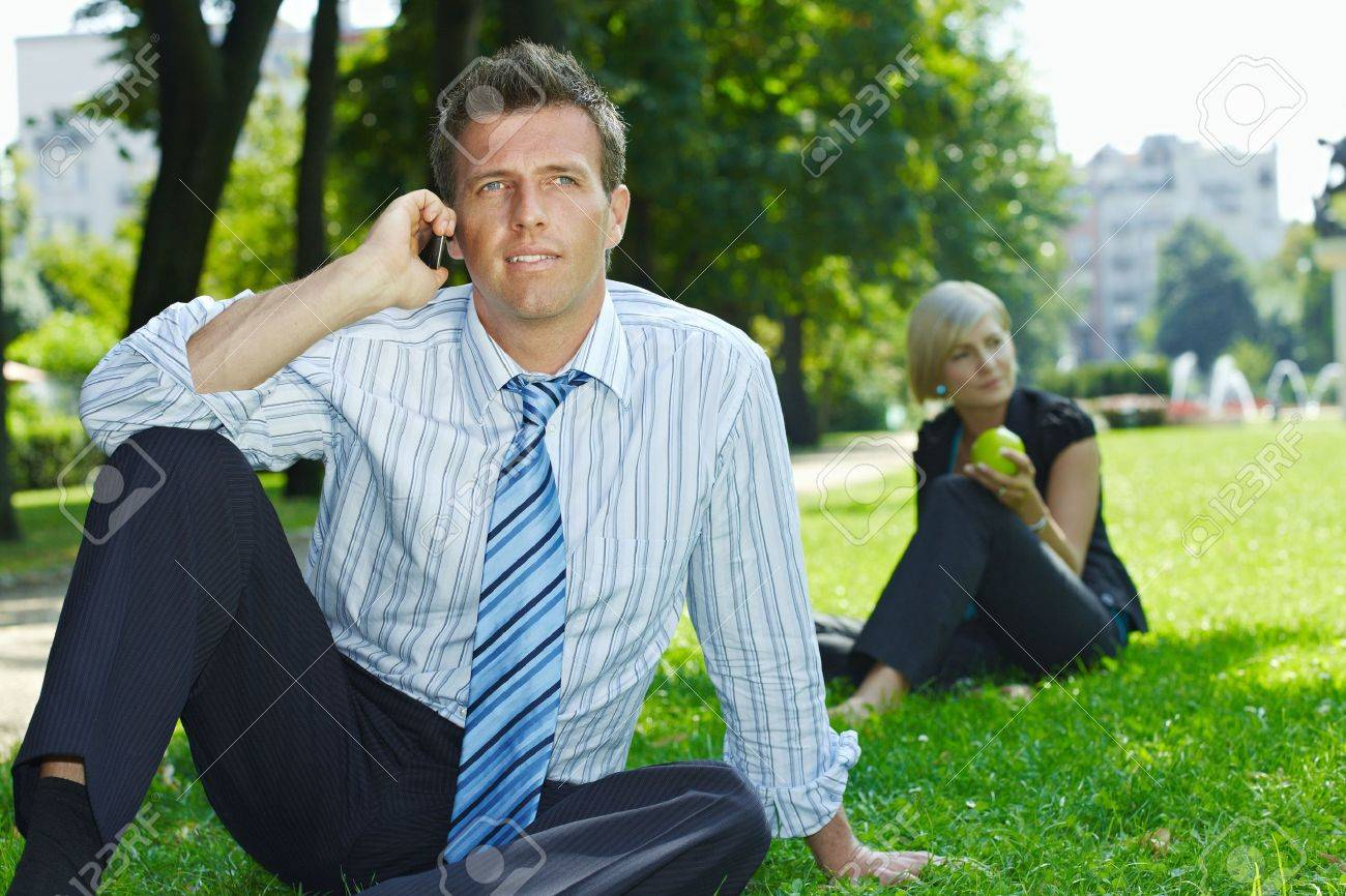 Businessman sitting in grass in park, talking on mobile. Busineswoman relaxing in the background. Stock Photo - 6308410