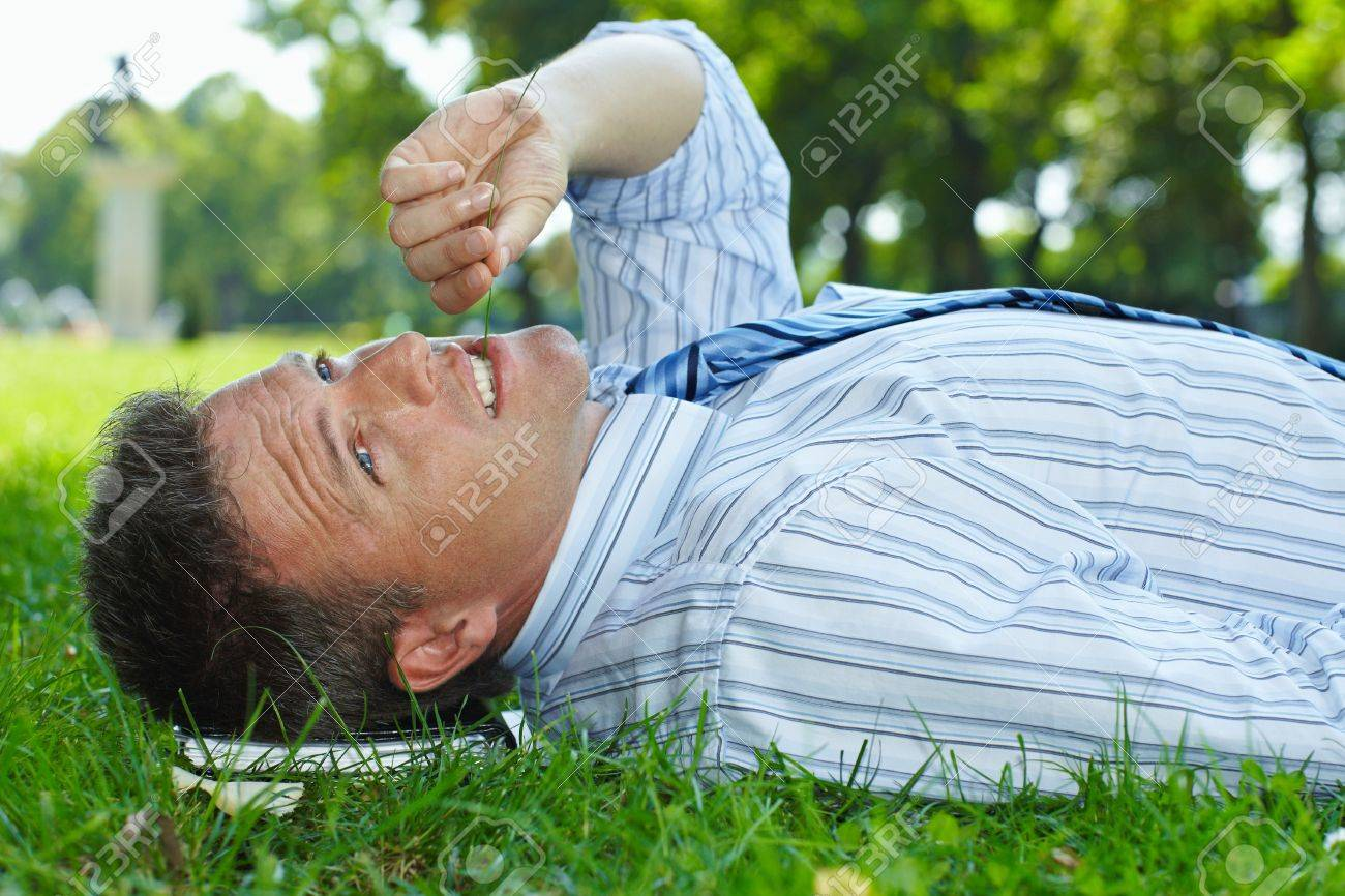 Closeup portrait of relaxed businessman lying in grass in park summertime. Stock Photo - 6308420