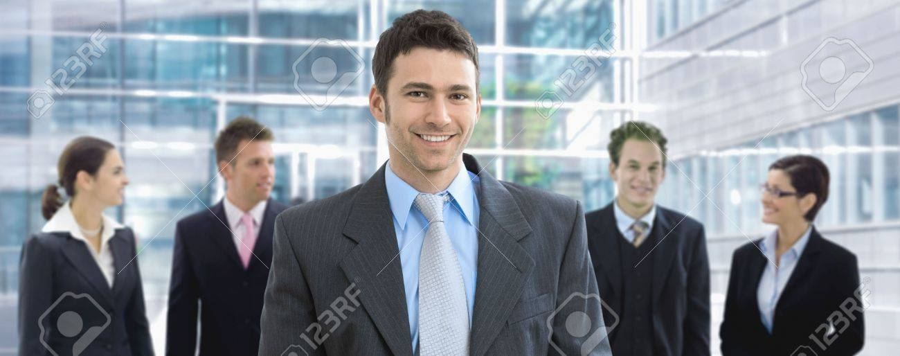 Portrait of happy businessman standing in office lounge, in front of business team, smiling. Stock Photo - 6338340