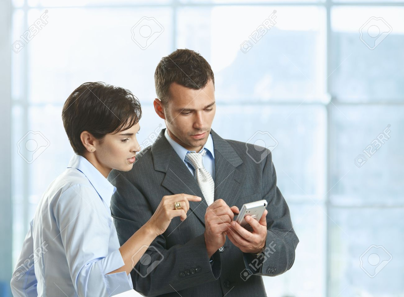 Two businesspeople standing in office lobby , looking at smart mobile phone, smiling. Stock Photo - 6338343