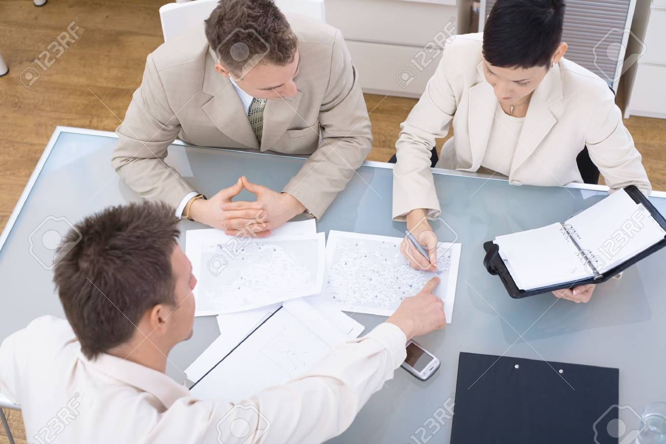 Businessteam of three working together, sitting around a desk, high angle view. Stock Photo - 6338487