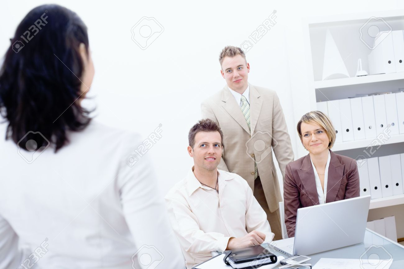 Four business people working in office. Three working together on laptop computer, looking up and smiing to fourth colleague. Stock Photo - 6338472