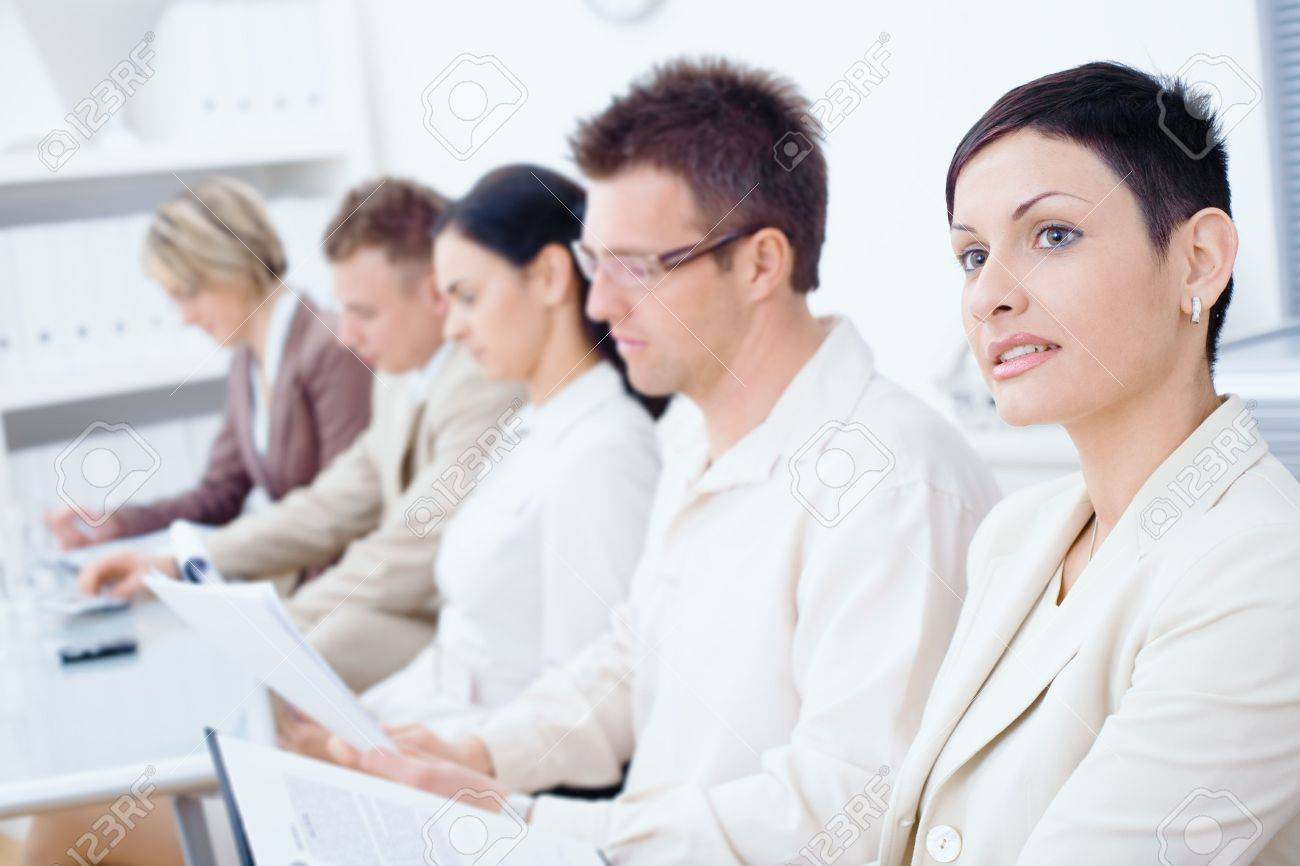 Five business people sitting in a row and writing notes on a business training. Selective focus placed on businesswoman in front. Stock Photo - 6338499