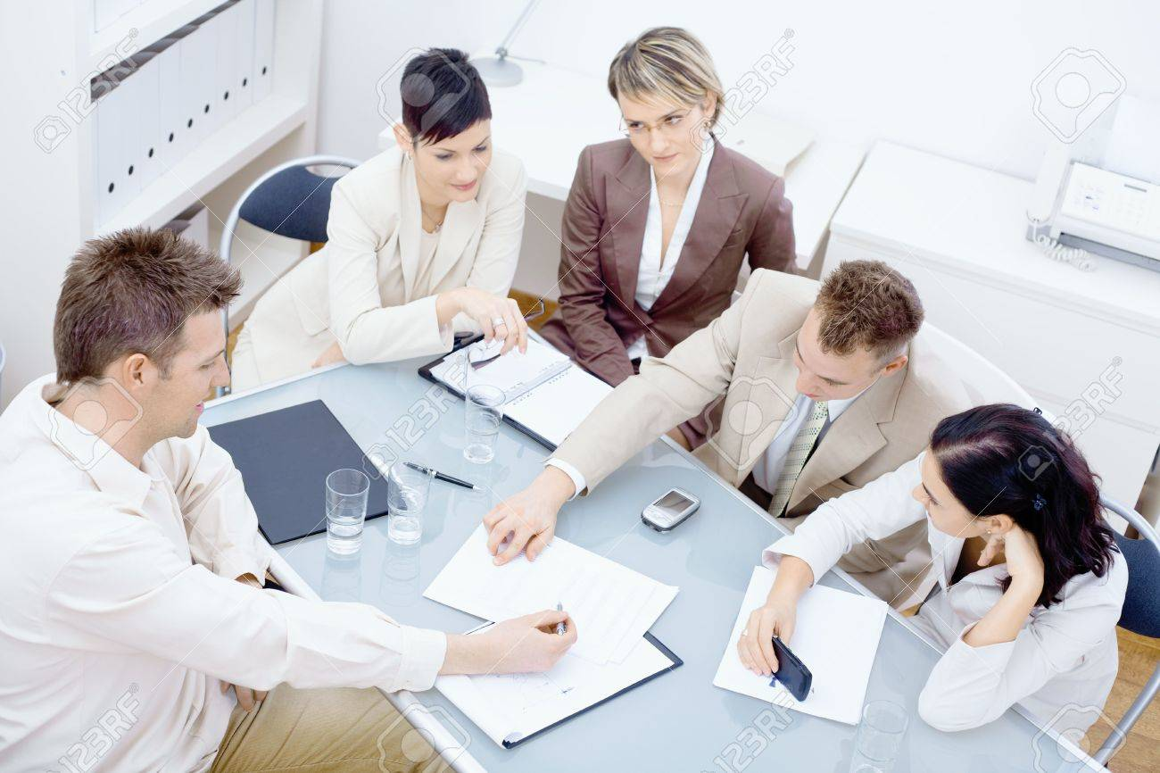 Five businesspeople sitting around table in office and having a meeting. Discussing business plans and writing notes on paper. Stock Photo - 6338480