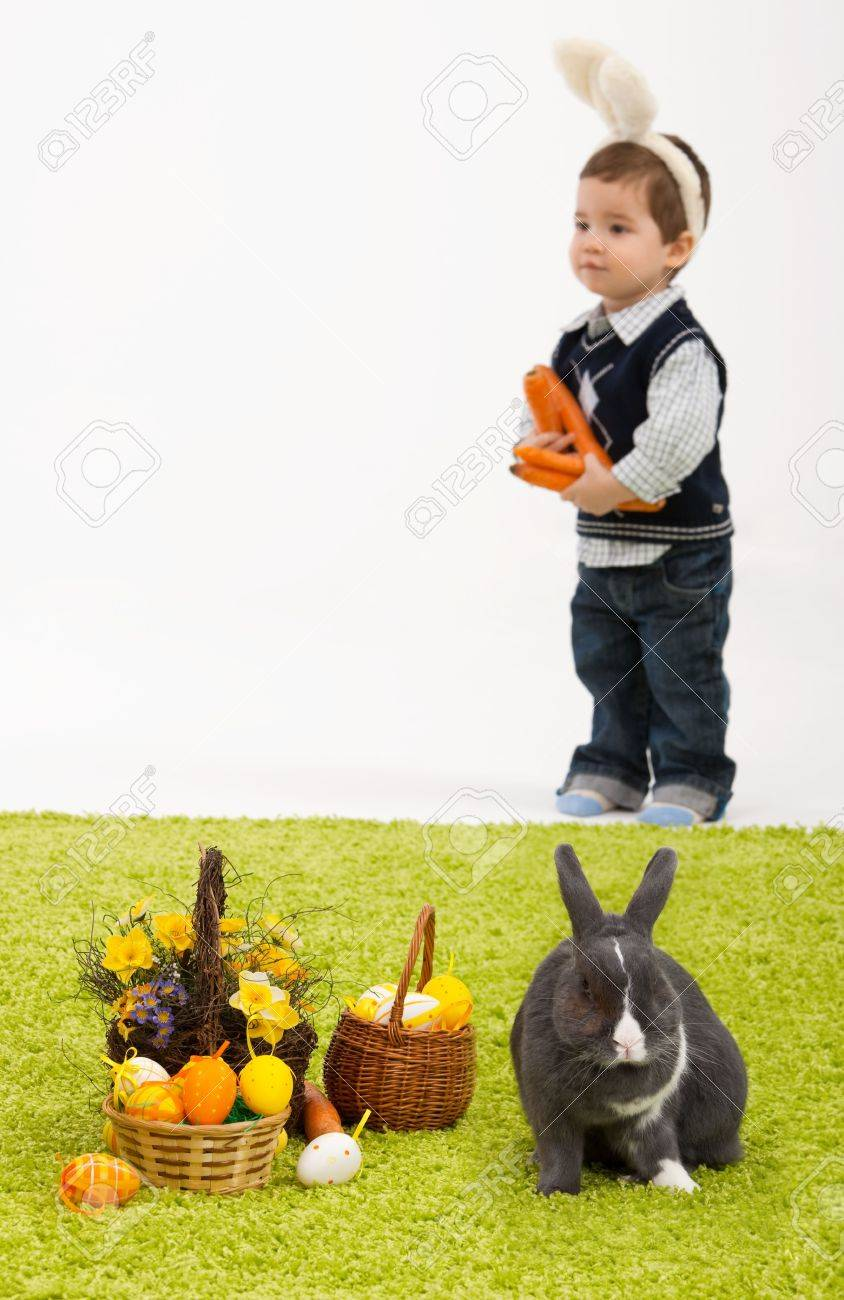 Little children playing with Easter bunny on green carpet. Focus placed on easter bunny in front, boy is out of focus. Stock Photo - 6338546