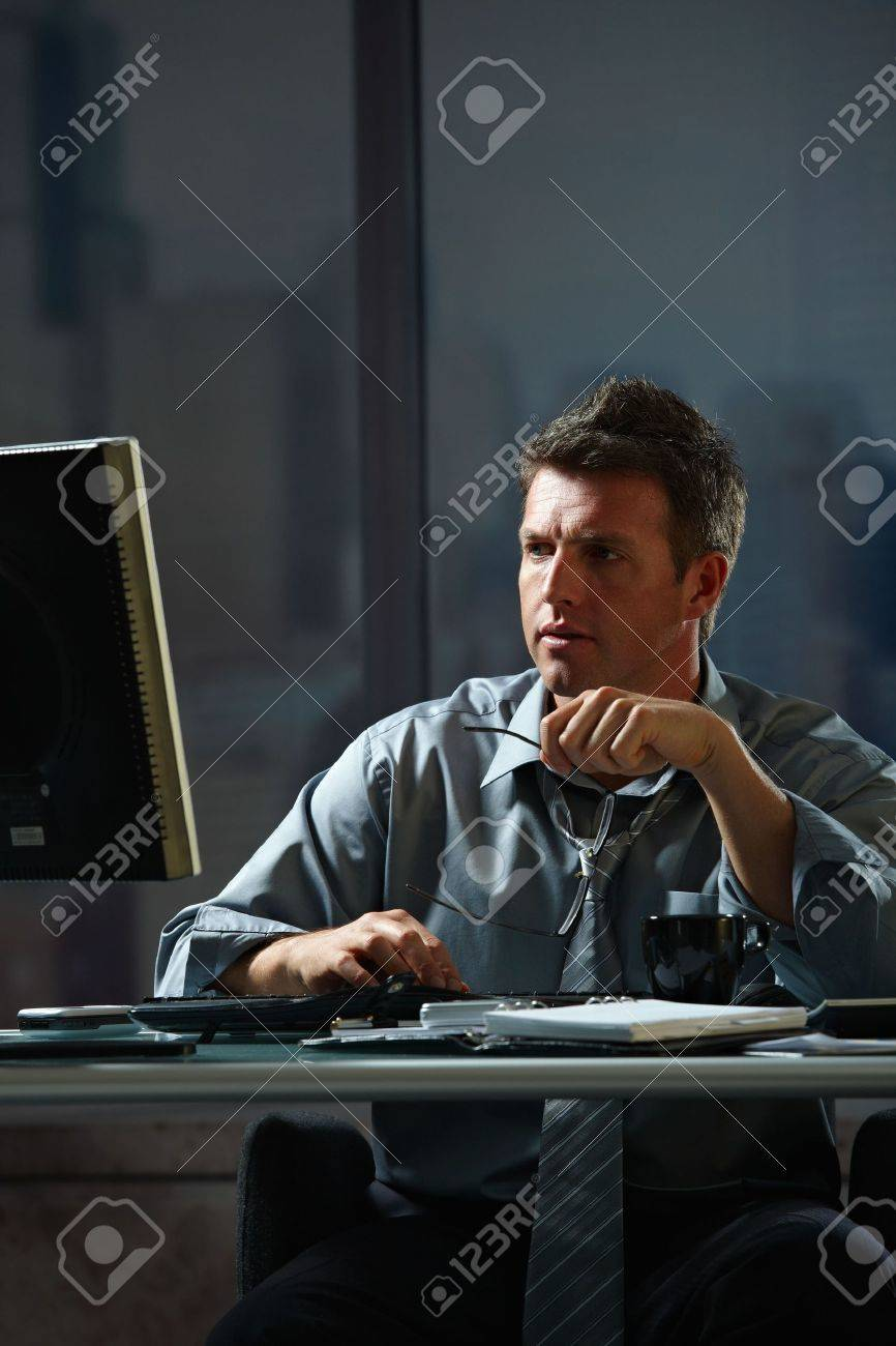 Tired businessman working late on computer in office holding glasses in hand. Stock Photo - 6338645