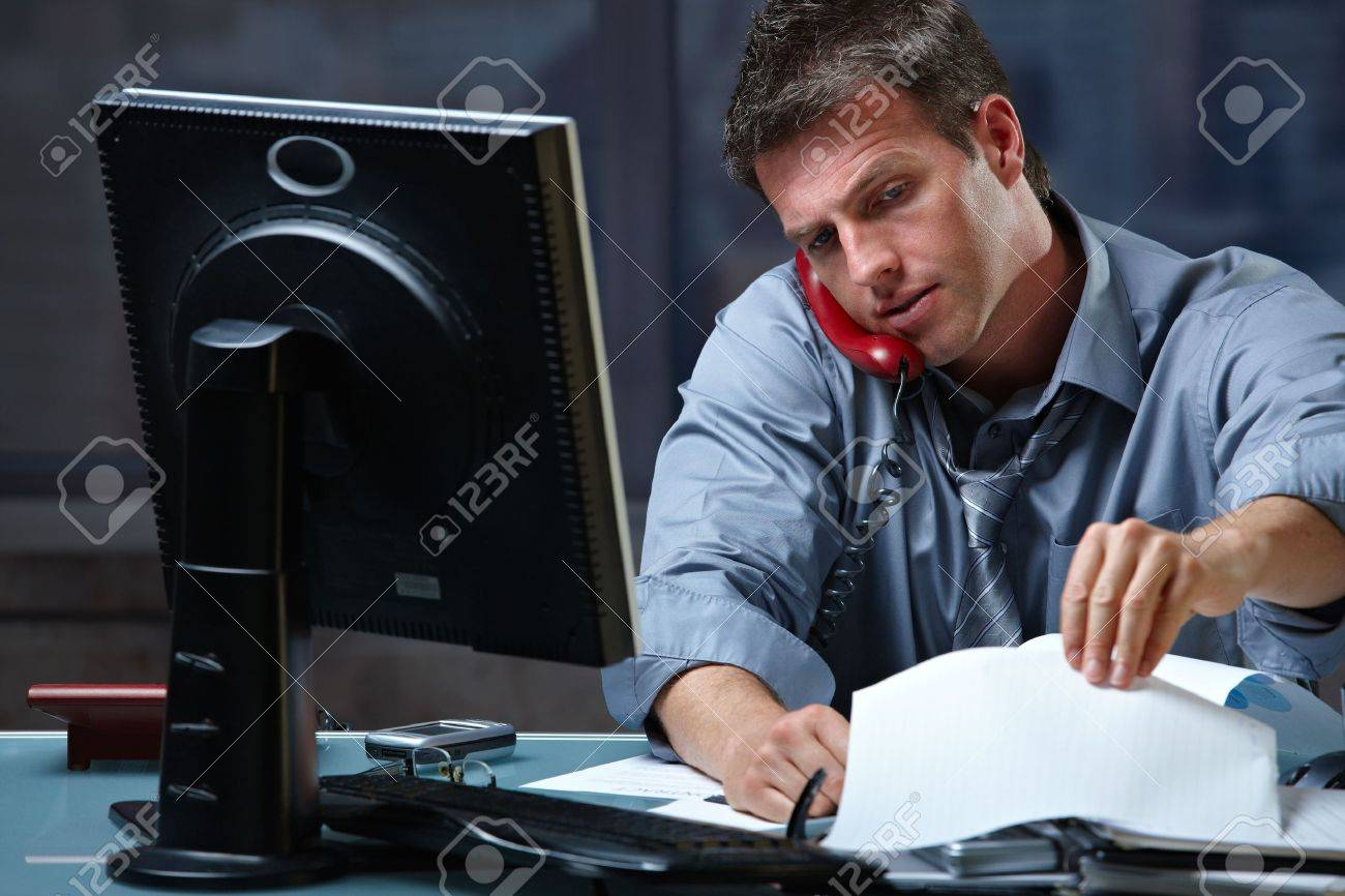 Mid-adult businessman speaking on landline phone working overtime in office checking papers. Stock Photo - 6338760