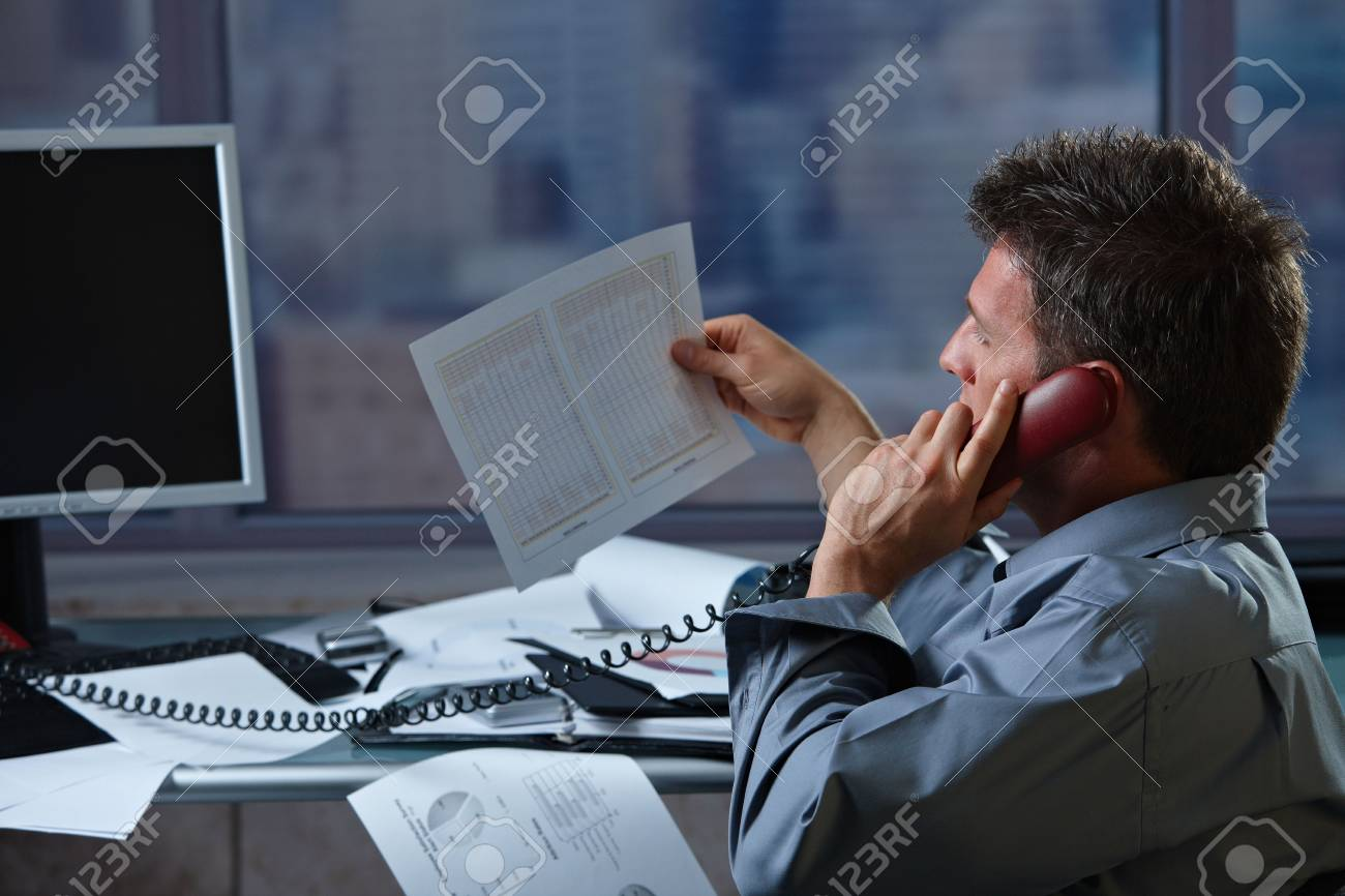 Mid-adult businessman talking on landline phone looking at business documents handheld in closeup. Stock Photo - 6338647