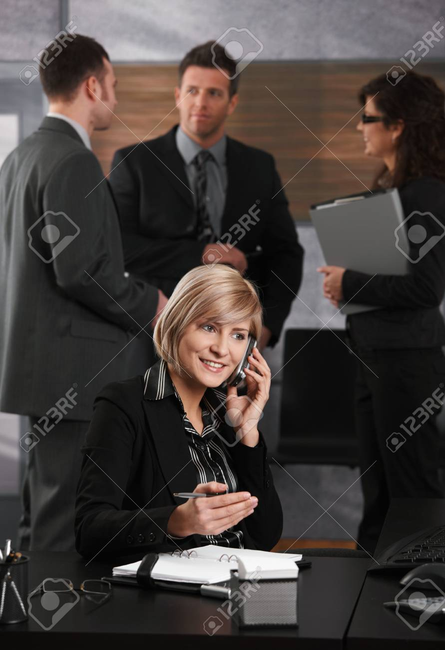 Happy young businesswoman sitting at office desk talking on mobile phone, smiling. Stock Photo - 6373568