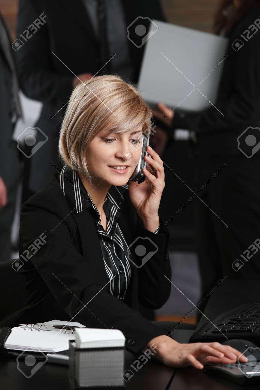 Happy young businesswoman sitting at office desk talking on mobile phone, using calculator, smiling. Stock Photo - 6373564