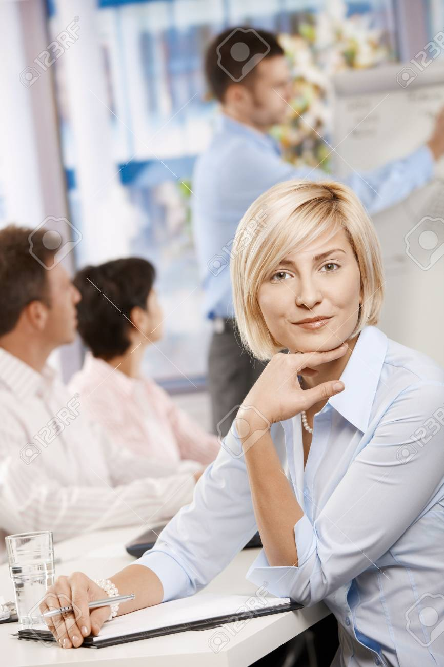 Young businesswoman sitting on business meeting in office making notes, looking at camera smiling. Stock Photo - 6373637