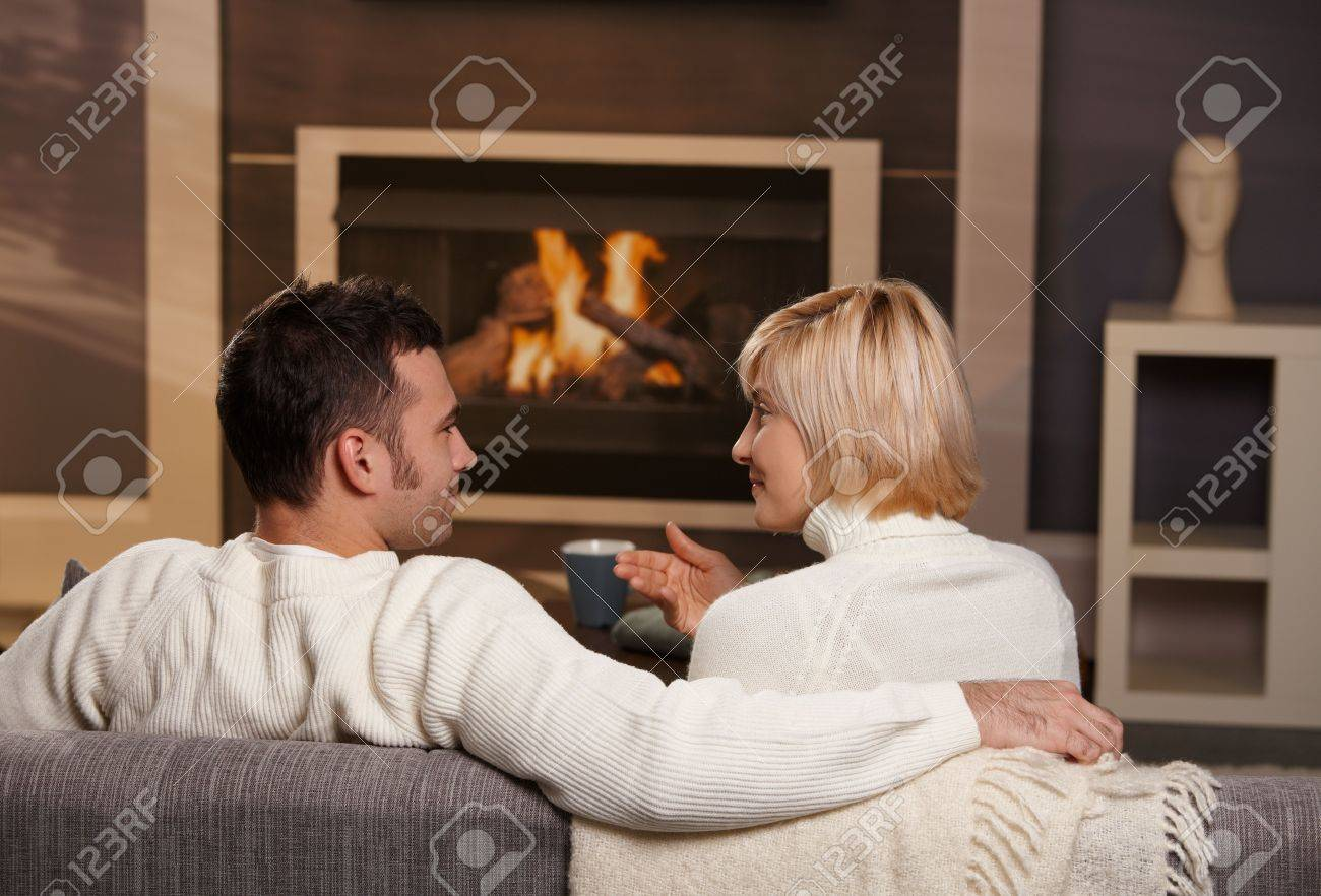 young romantic couple sitting on sofa in front of fireplace at