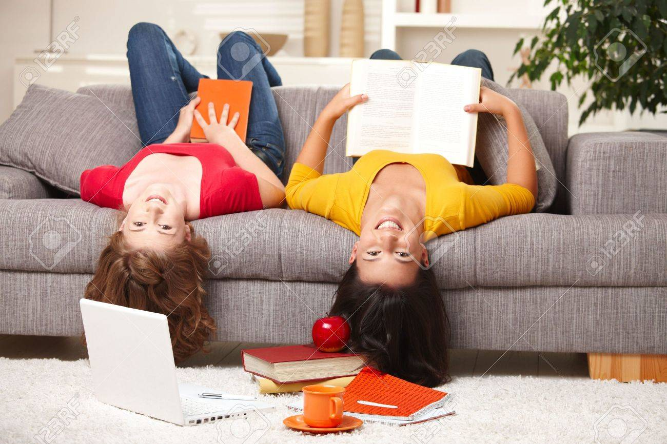 Happy teen girls sitting upside down on sofa smiling looking at camera holding books. Stock Photo - 6373949