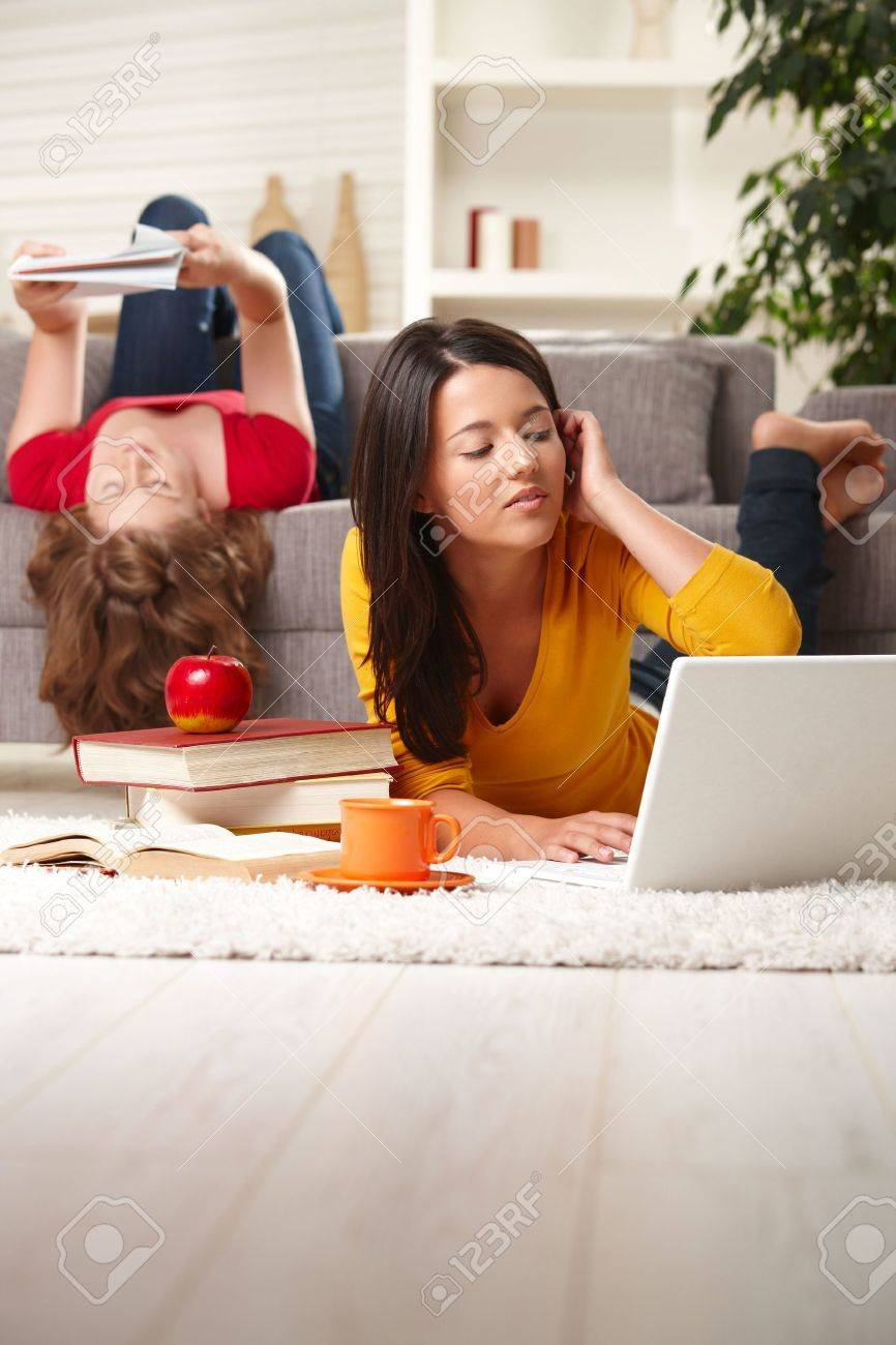 Teenage girls studying at home in living room lying on sofa and floor with books and laptop. Stock Photo - 6373898