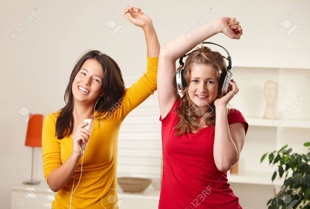 Teen girls listening to music having fun together at home dancing smiling, eye contact. Stock Photo - 6373858