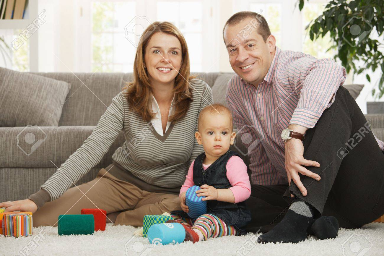 Happy family sitting on floor smiling at camera with baby girl. Stock Photo - 6374558