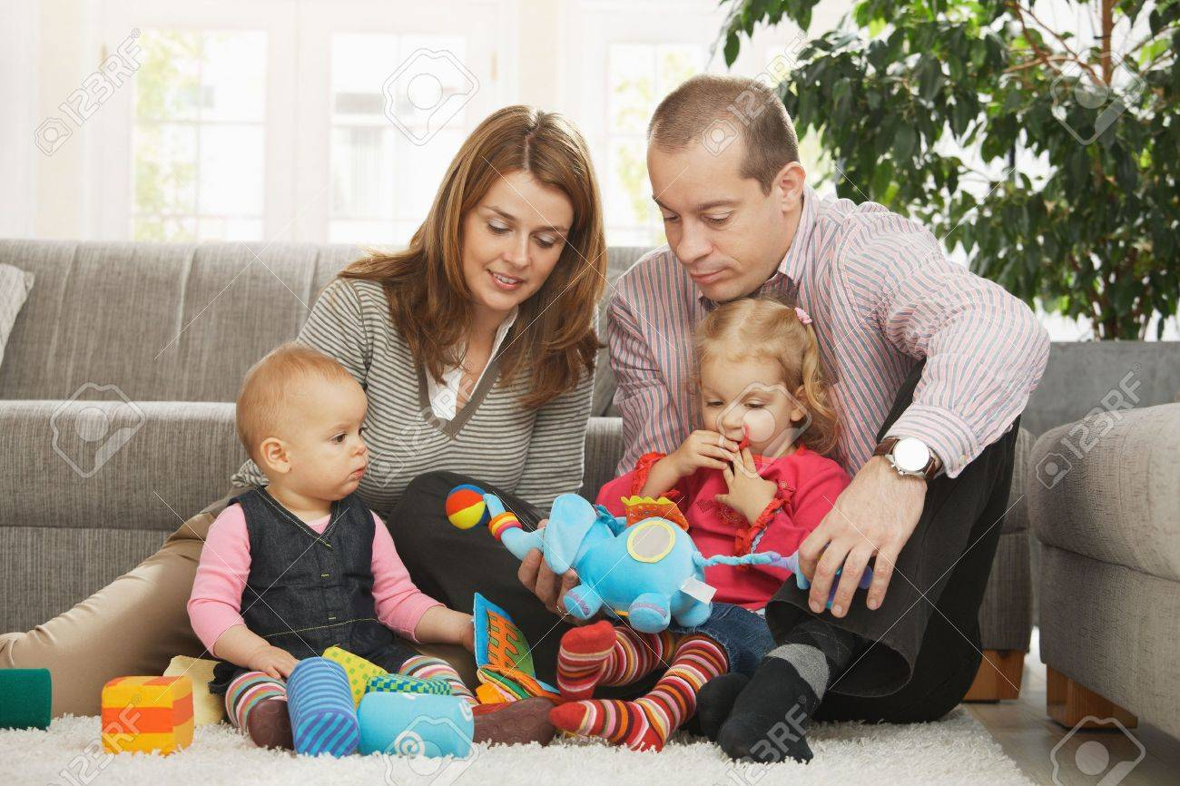Happy family with two children playing on floor in living room at home sitting on floor in front of sofa. Stock Photo - 6374540