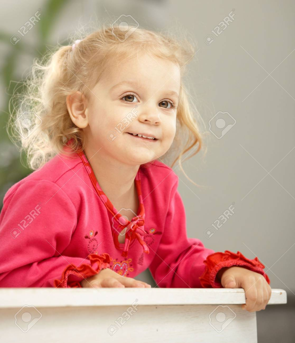 Happy two-year-old leaning on counter smiling. Stock Photo - 6374431