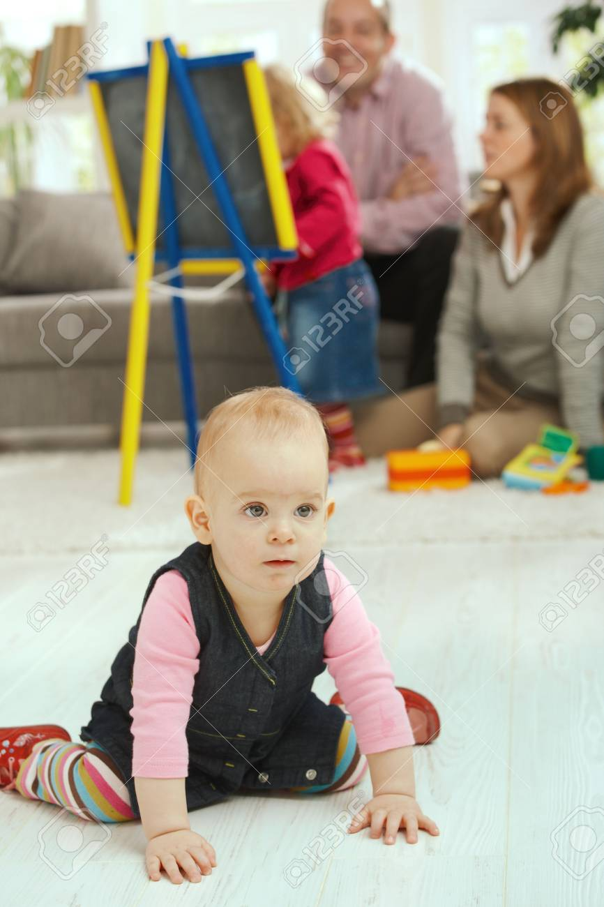 Baby girl crawling on living room floor, family in the background. Stock Photo - 6374424