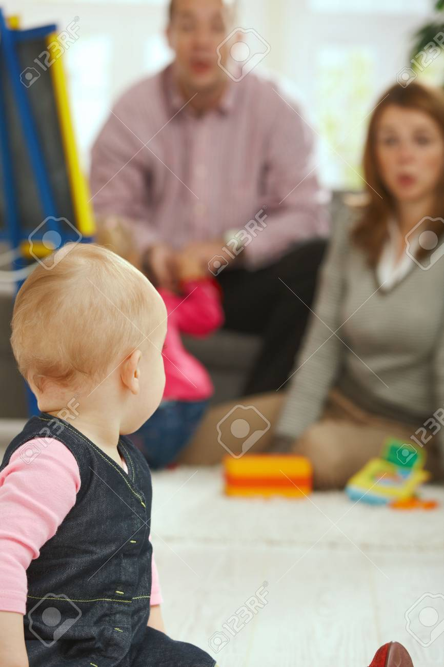 Baby girl turning back looking at parents in the background. Stock Photo - 6374410