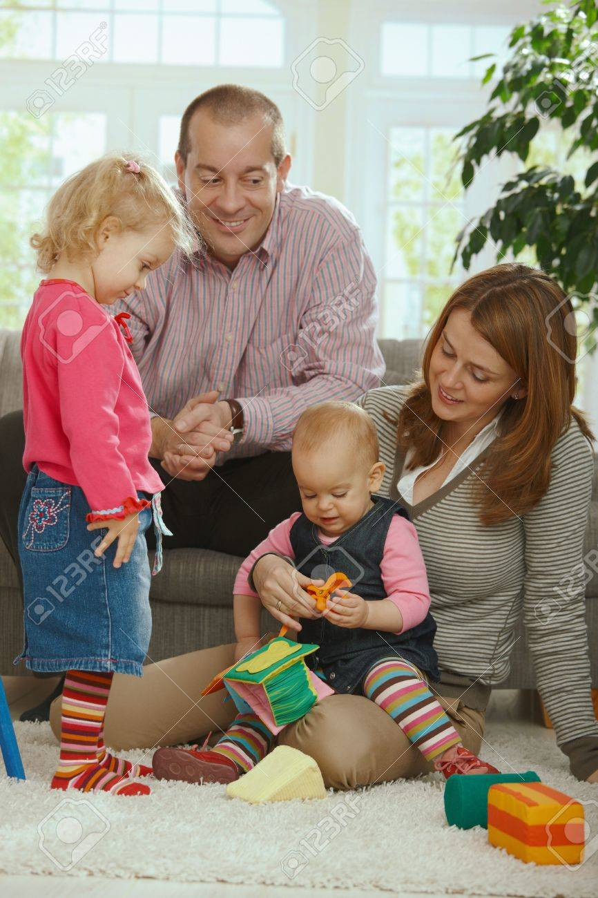 Portrait of happy smiling family of dad, mum and two baby girls at home. Stock Photo - 6374560