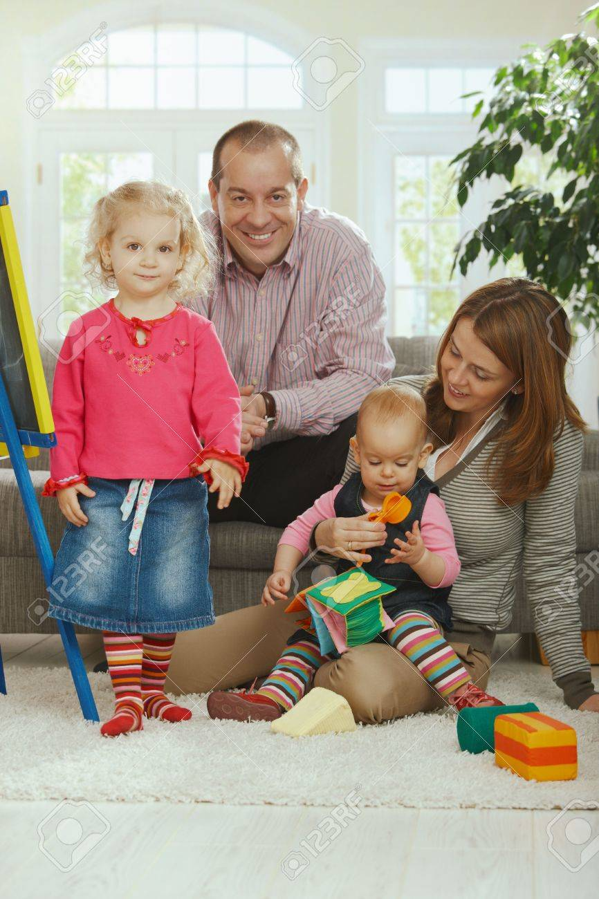 Portrait of happy smiling family of dad, mum and two baby girls at home. Stock Photo - 6374524