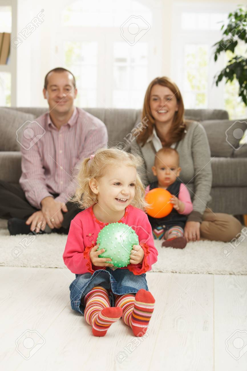 Smiling little girl holding ball at home with family in background. Stock Photo - 6374451