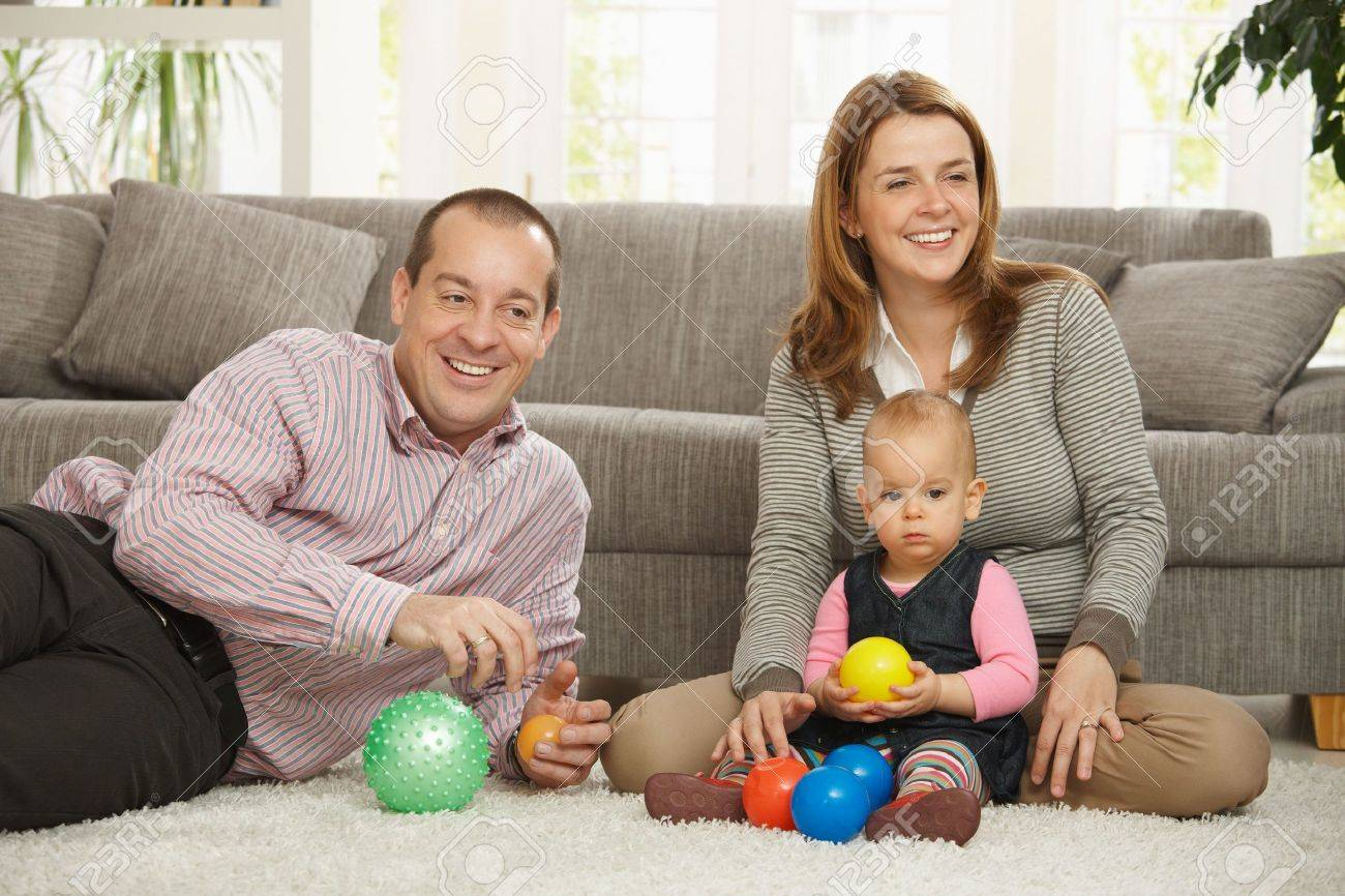 Happy smiling parents sitting with baby girl holding ball in hands at  home. Stock Photo - 6374545