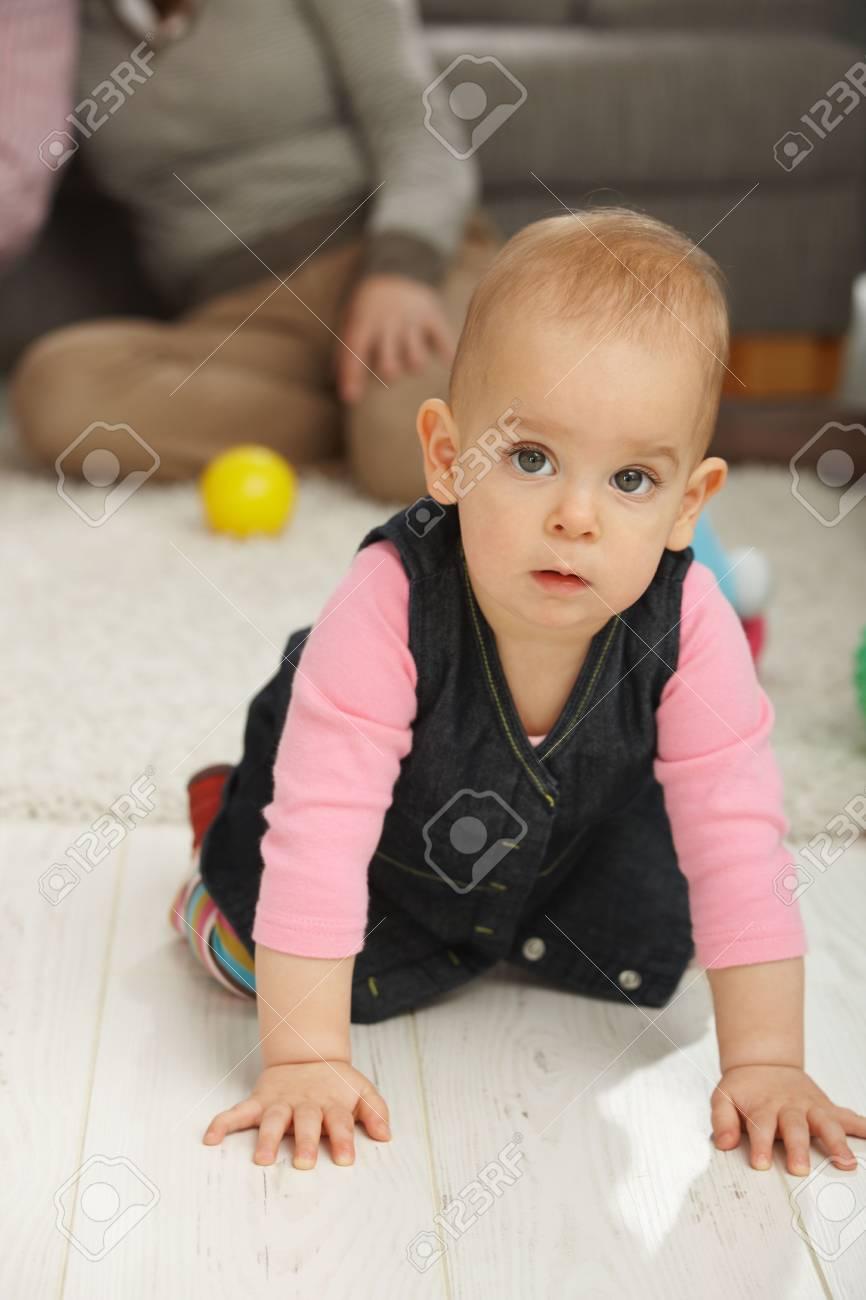 Portrait of cute baby girl kneeling on living room floor looking aside. Stock Photo - 6374418