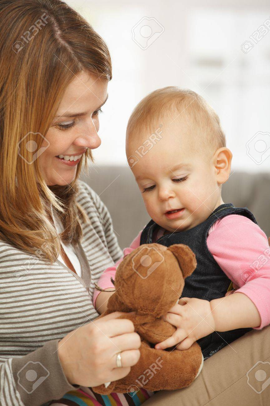 Happy mum and baby girl cuddling holding teddy bear. Stock Photo - 6374544