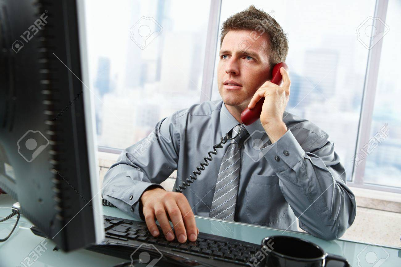 Determined businessman discussing computer work on landline phone while looking at screen typing on keyboard at office desk. Stock Photo - 6397060