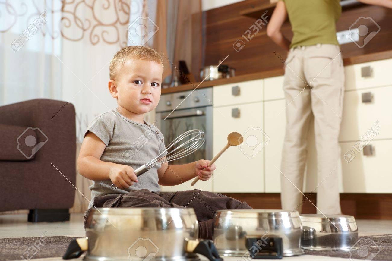 Little boy sitting on carpet in kitchen playing with cooking pots, mother preparing food in background. Stock Photo - 6401229