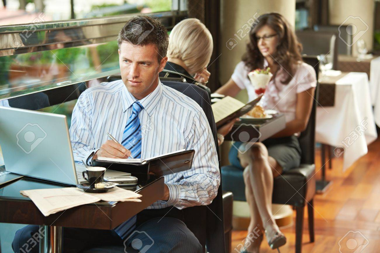 Businessman sitting at table in cafe using laptop computer, writing notes. Young women having sweets in the background. Stock Photo - 6437588