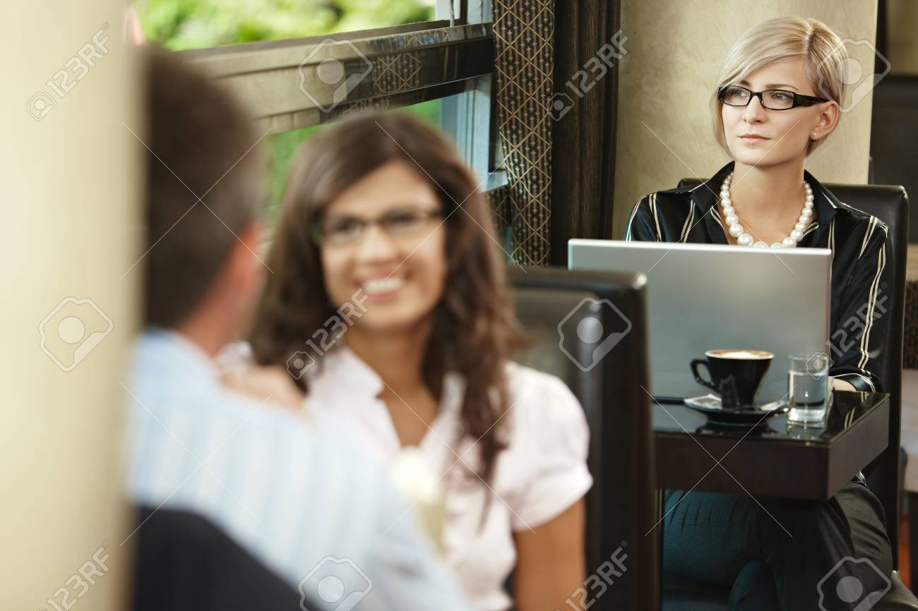 Young woman sitting at table in cafe, using laptop computer. Stock Photo - 6432783