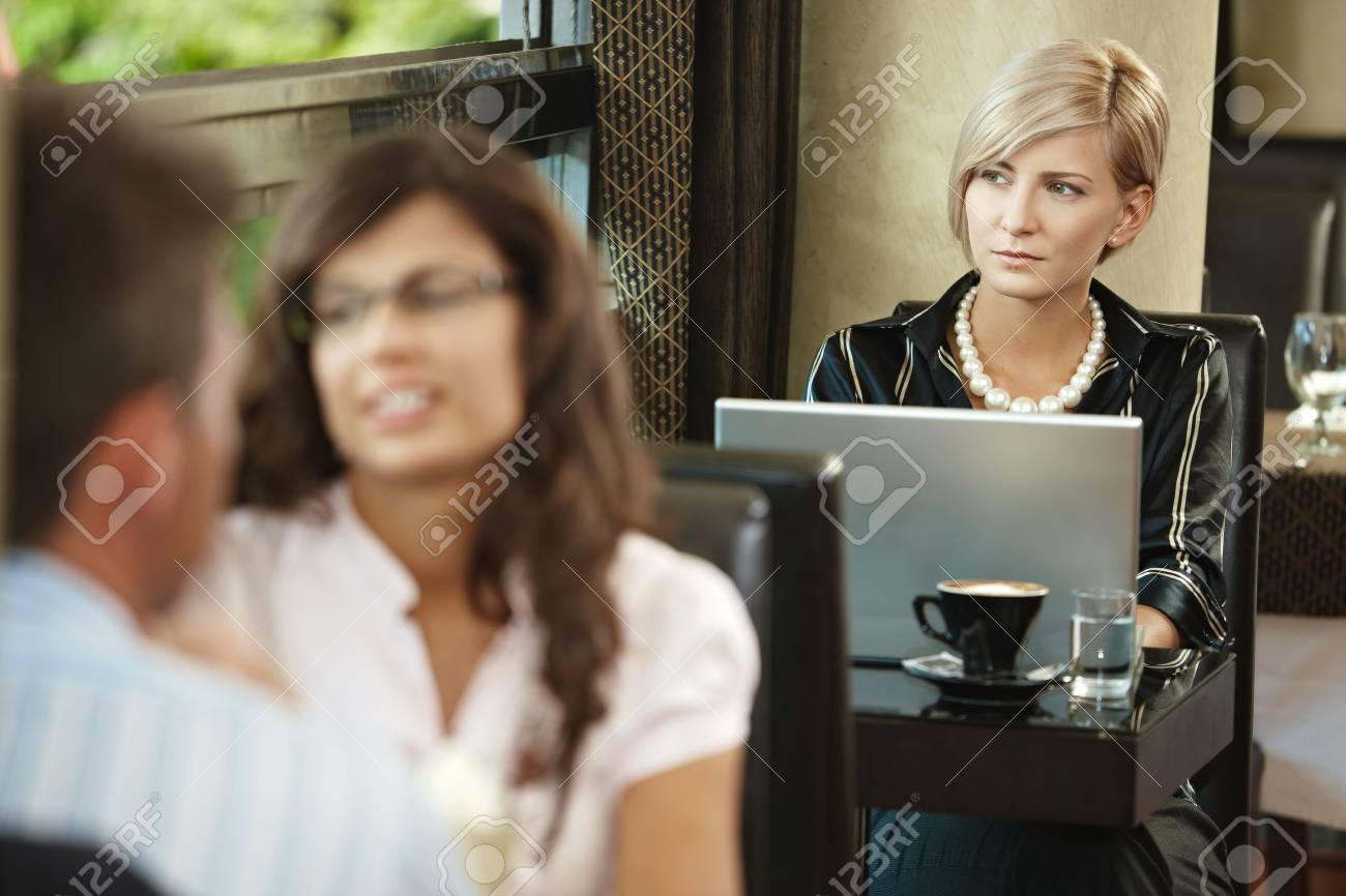 Young woman sitting at table in cafe, using laptop computer. Stock Photo - 6432795