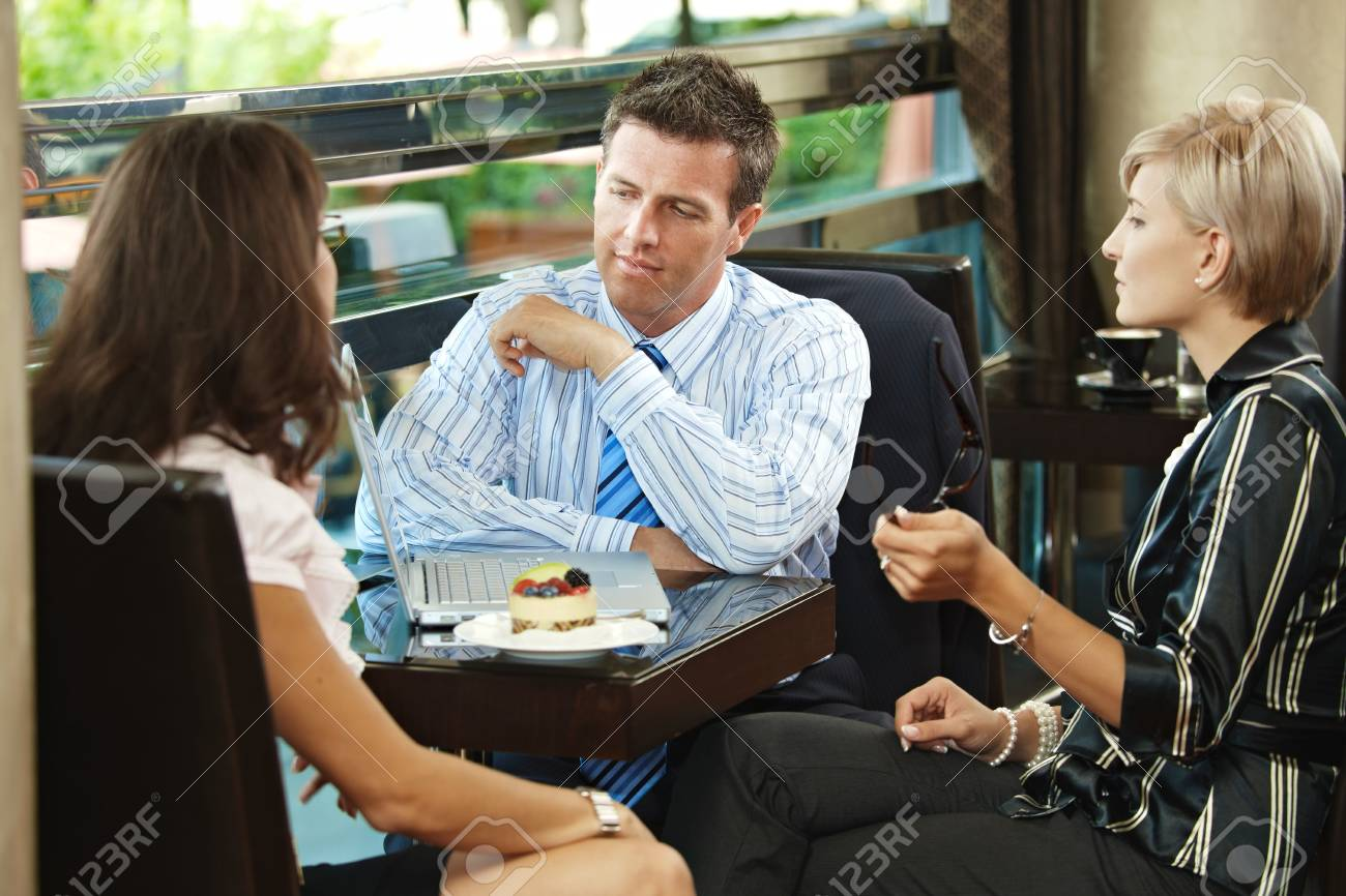 Young businessman and businesswomenhaving a meeting in cafe. Stock Photo - 6432787