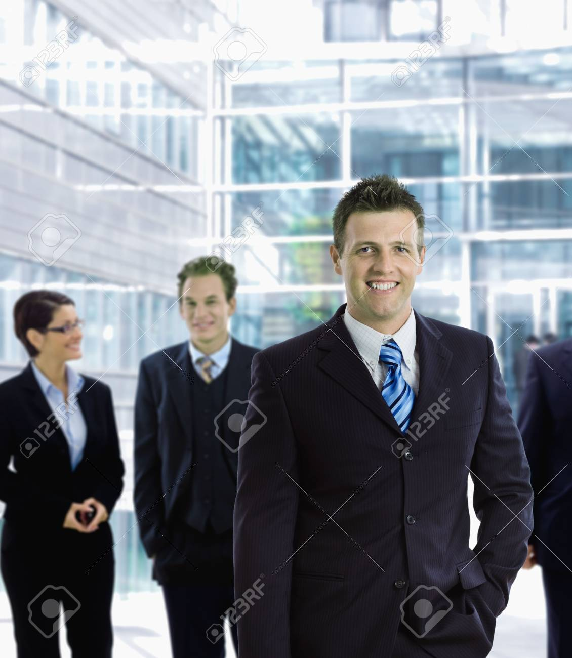 Happy businessman standing in front of other businesspeople, out of office building, smiling. Stock Photo - 6438115