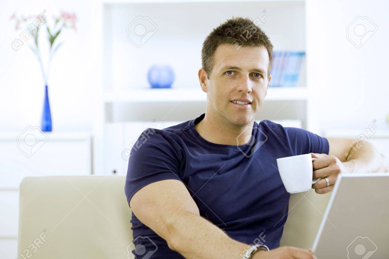 Relaxed young man drinking coffee at home, sitting on couch. Stock Photo - 6463460