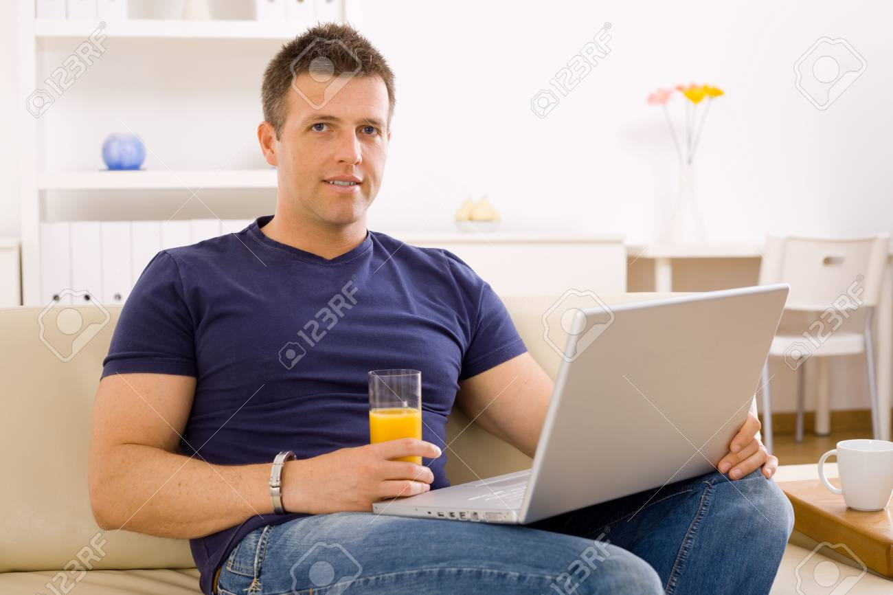 Young man sitting on sofa at home and using laptop computer. Stock Photo - 6463473