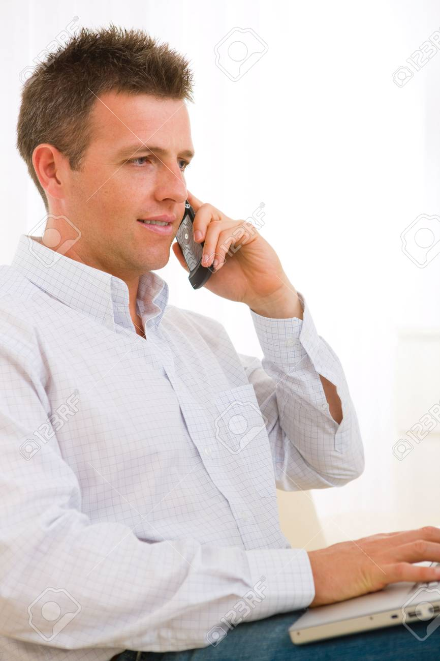 Casual businessman working at home sitting on couch, using laptop computer, talking on mobile phone. Stock Photo - 6463536
