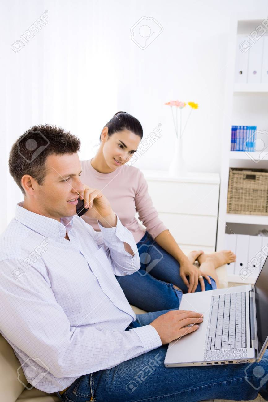 Young couple using laptop computer at home, sitting on couch. Man talkin on mobile phone. Stock Photo - 6463521
