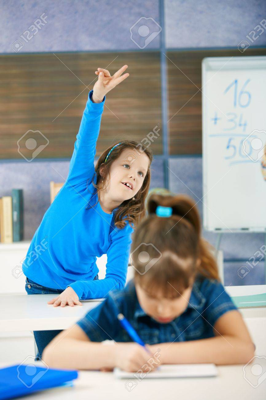 Schoolgirl in focus standing up in back row of class raising hand to answer question. Stock Photo - 6463683
