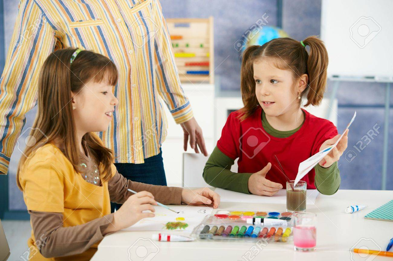Elementary age children sitting around desk enjoying painting with colors in art class at primary school classroom. Stock Photo - 6463753