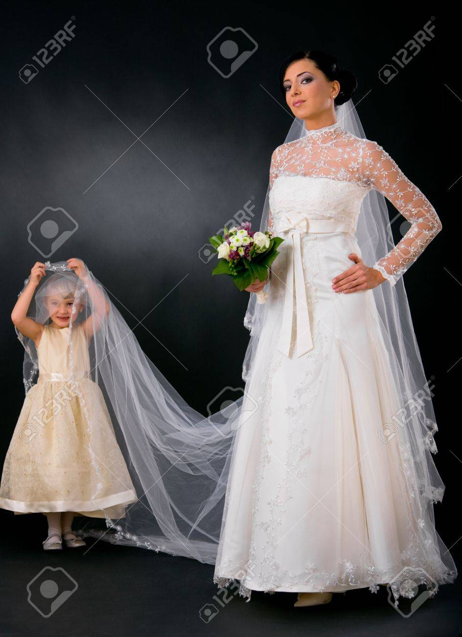 Bride posing in romantic white wedding dress, holding bouquet of flowers, little bridesmaid holding her veil. Stock Photo - 6508782