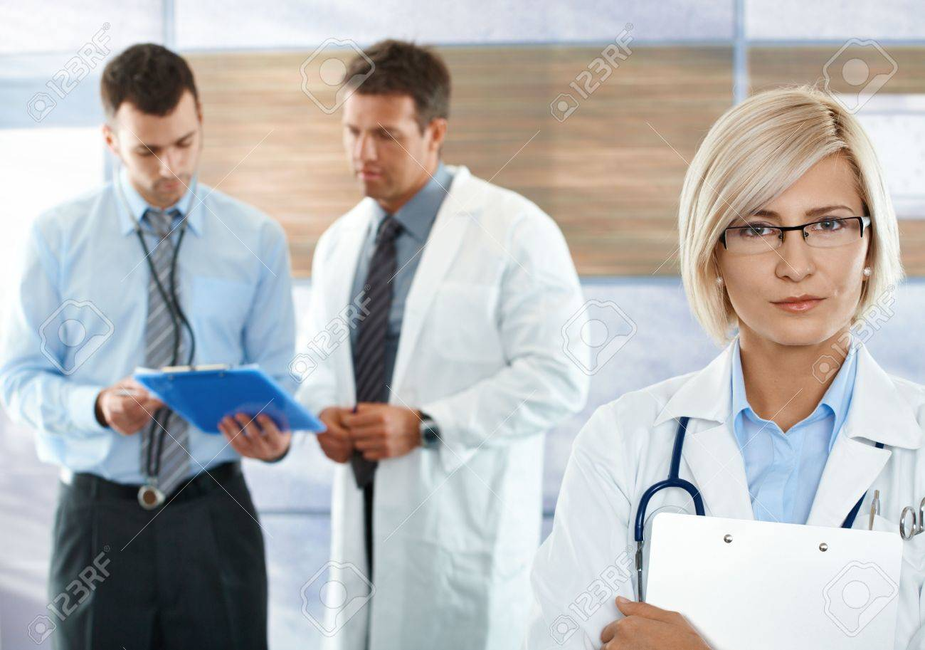 Healthcare workers on hospital corridor female doctor in front looking at camera. Stock Photo - 6527182
