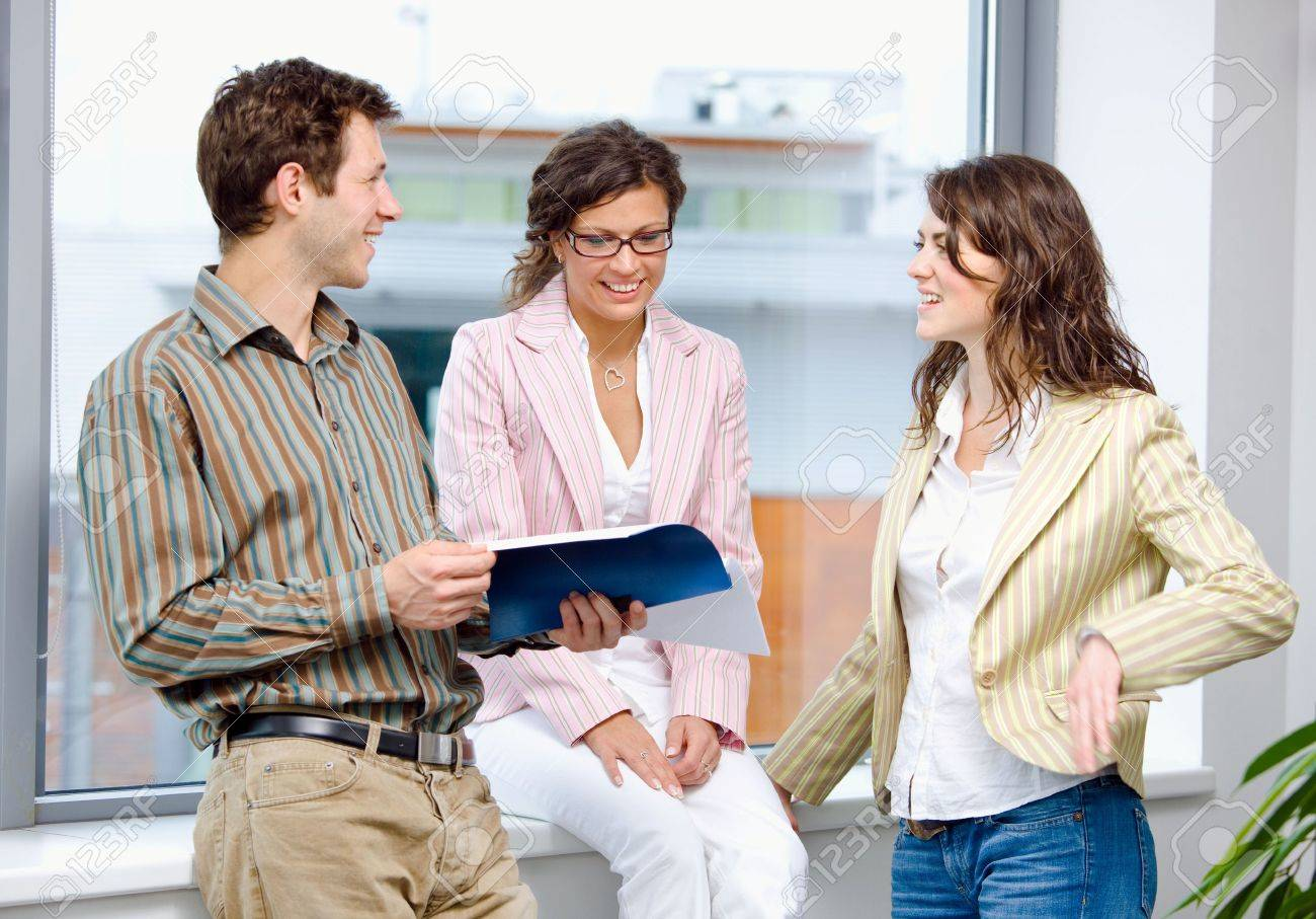 Happy young businesspeople having meeting at office and reading documents, smiling. Stock Photo - 6550700