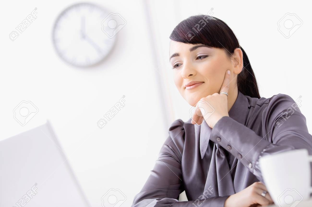 Young businesswoman thinking over her laptop, leaning on her hand, smiling. Stock Photo - 6593002
