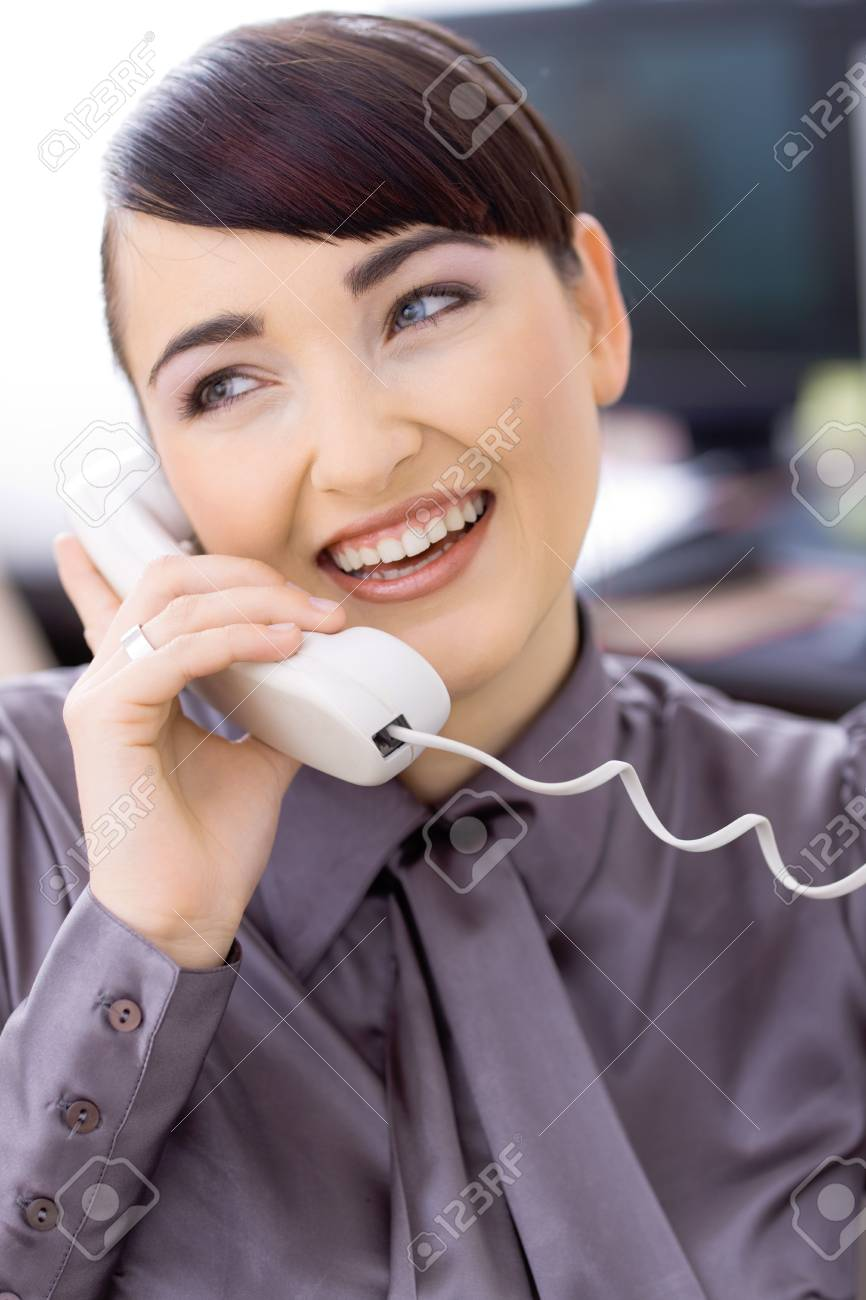 Happy young businesswoman talking on landline phone in office, smiling. Stock Photo - 6592984